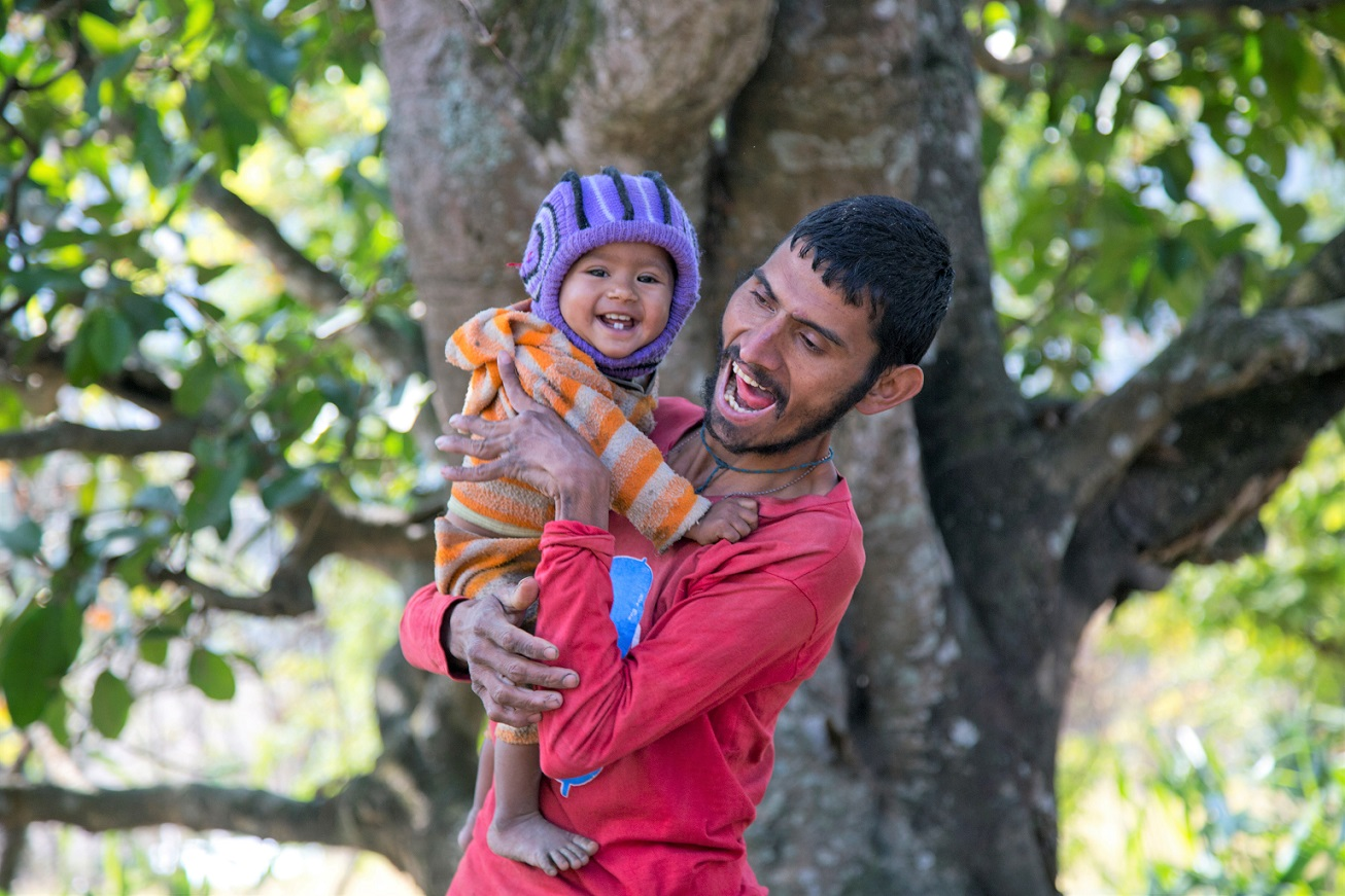 Nepalise man smiling with baby