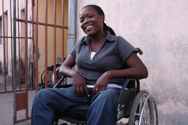 Een glimlachende vrouw in een rolstoel