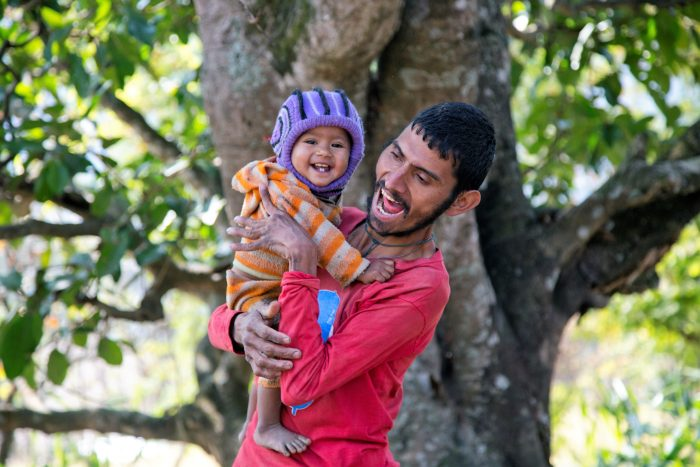 Nepalese man smiling and holding a smiling baby
