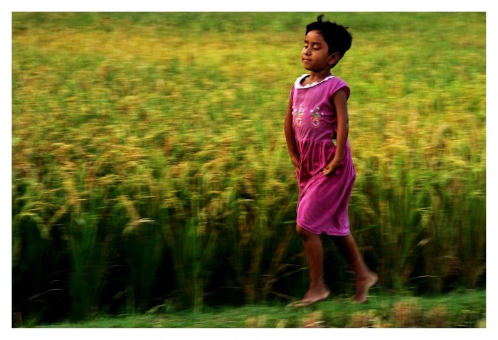 A girl skipping next to a field