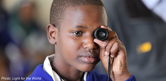 Young boy holding a loupe in front of his left eye
