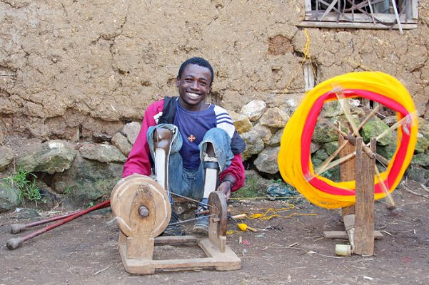 Broadly smiling man with spinning wheel and crutches