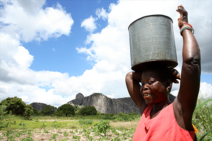 African woman carrying a large metal pot on her head