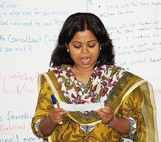 A woman is ginving a presentation in front of a whiteboard
