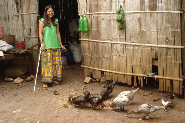 Blind woman stands in front of her house whilst geese peck the ground around her for food.