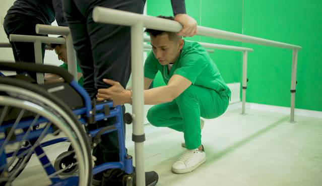 A doctor examines the legs of a person who uses a wheelchair