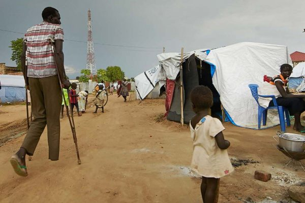 Photo of a man on crutches walking through a refugee camp, watched by a little girl.